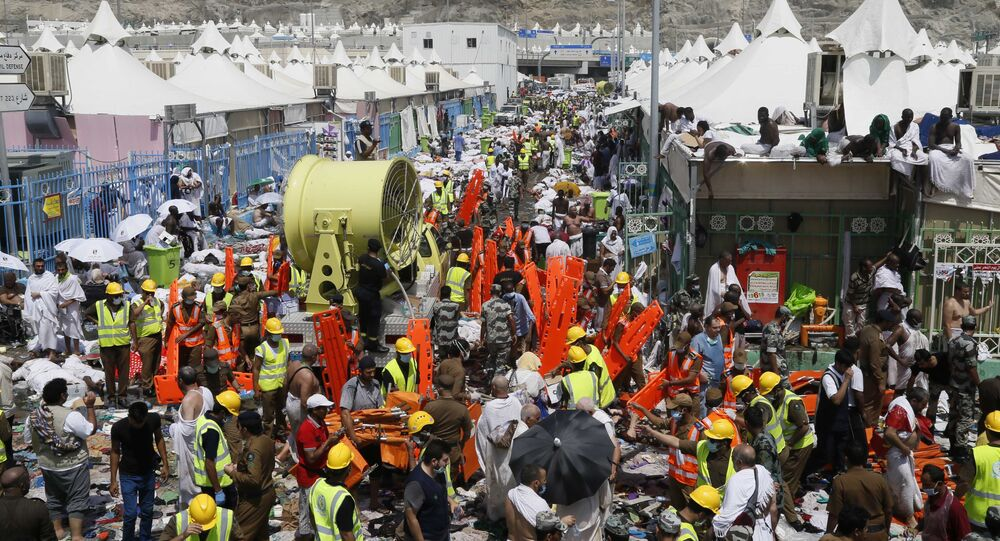 Muslim pilgrims and rescuers gather around the victims of a stampede in Mina, Saudi Arabia during the annual hajj pilgrimage on Thursday, Sept. 24, 2015