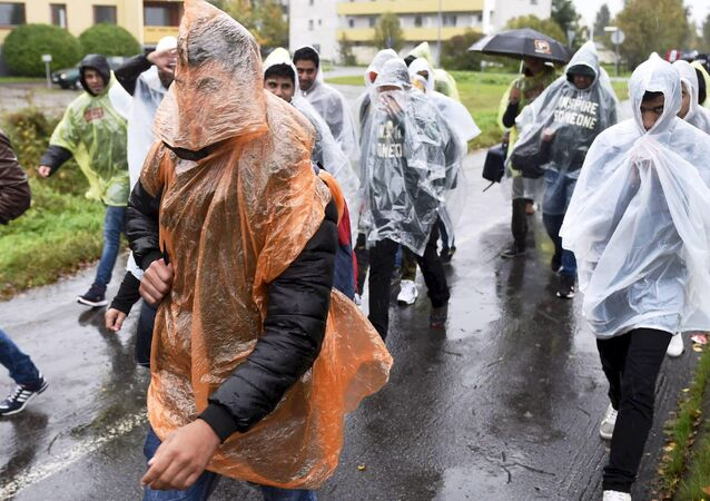 Refugees walked in heavy rain from a public transport centre to Lappia-building refugee reception centre in Tornio, northwestern Finland