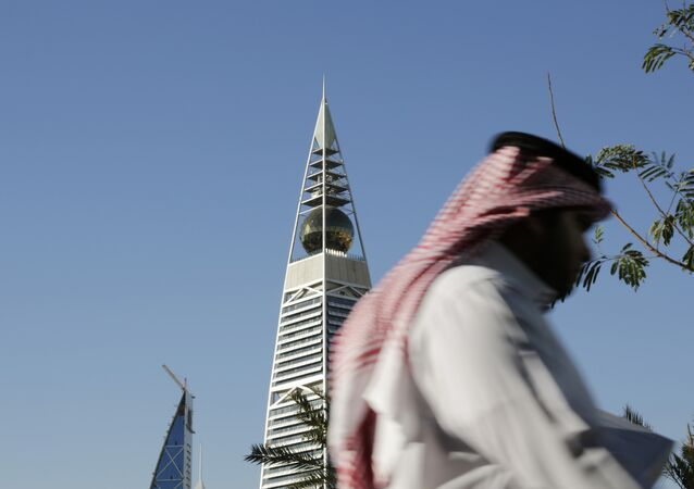 A Saudi man passes the al-Faisaliya tower in Riyadh, Saudi Arabia