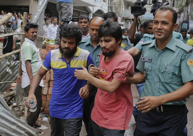 Suspected members of the banned Islamic militant outfit Ansarullah Bangla Team are escorted by policemen along with another suspect from a court in Dhaka, Bangladesh, Wednesday, Aug. 19, 2015.