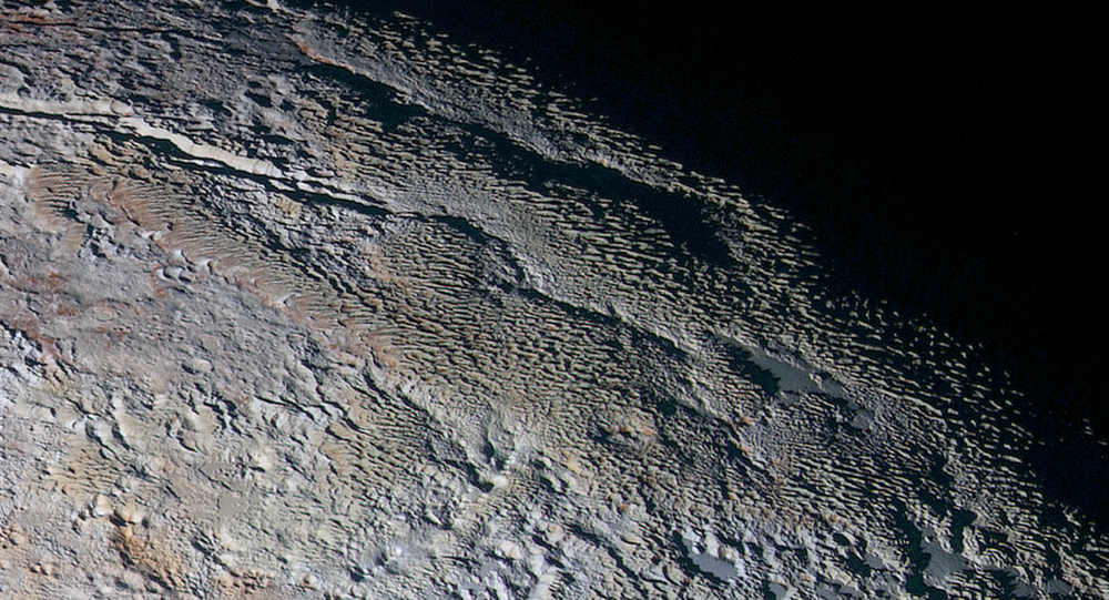 Rounded and bizarrely textured mountains, informally named the Tartarus Dorsa, rise up along Pluto's day-night terminator and show intricate but puzzling patterns of blue-gray ridges and reddish material in between.