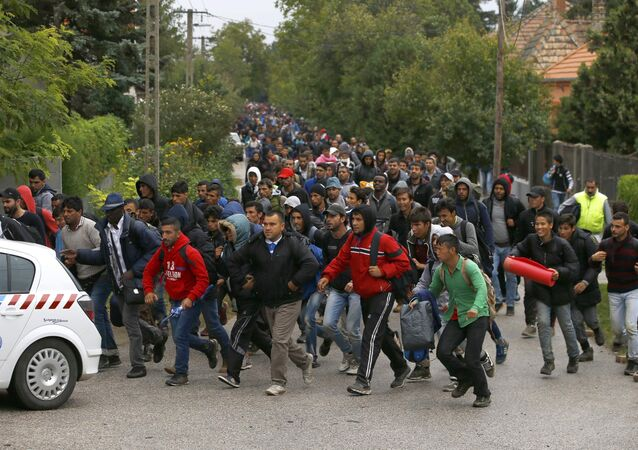 Migrants run as they follow a police vehicle on their way to the Austrian border in Nickelsdorf from Hegyeshalom, Hungary September 25, 2015.