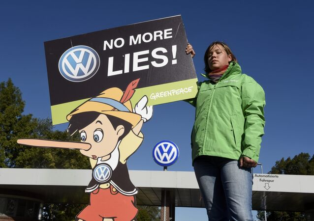 A Greenpeace activist holds a banner during a protest in front of Volkswagen's Sandkamp gate in Wolfsburg, Germany September 25, 2015.