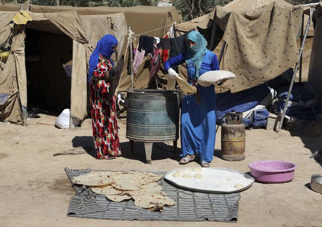 Iraqi women bake bread at al-Takia refugee camp in Baghdad, Iraq, Thursday, Sept. 24, 2015