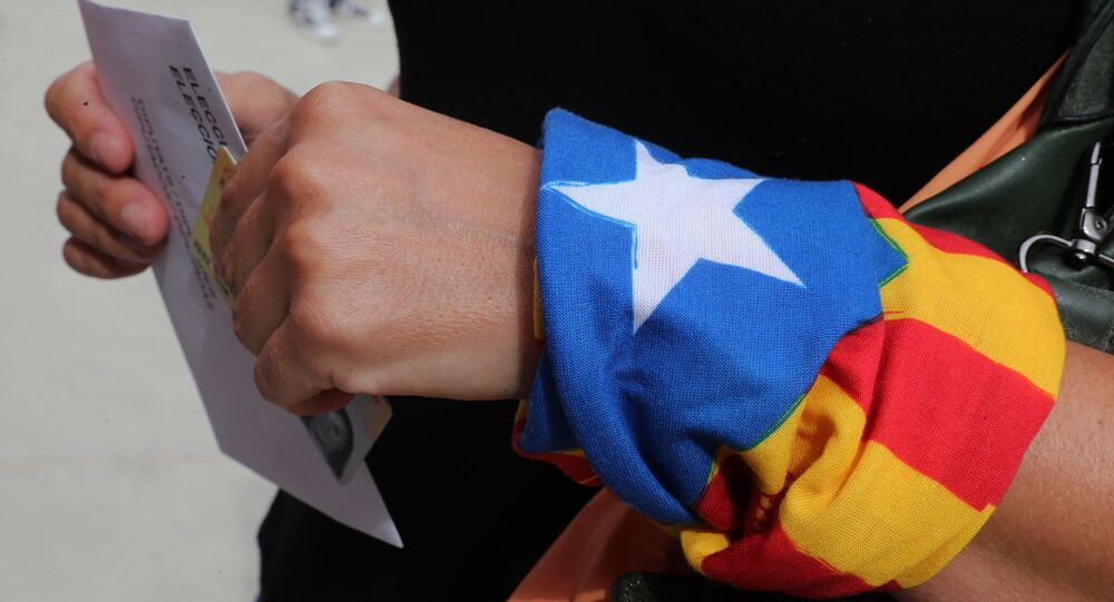 A woman with an Estelada (Catalan pro-independece flag) tied to her wrist waits for casting her ballot for the regional election at a polling station in Badalona on September 27, 2015