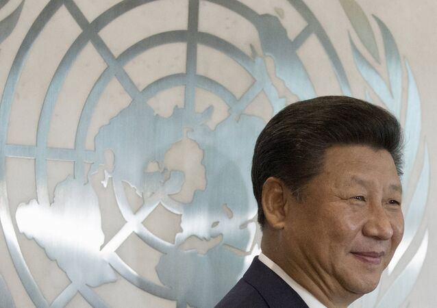 Chinese President Xi Jinping stands in front of the United Nations emblem as he poses for a photograph with U.N. Secretary-General Ban Ki-moon (unseen) after addressing the United Nations Sustainable Development Summit 2015 at the United Nations headquarters in Manhattan, New York September 26, 2015