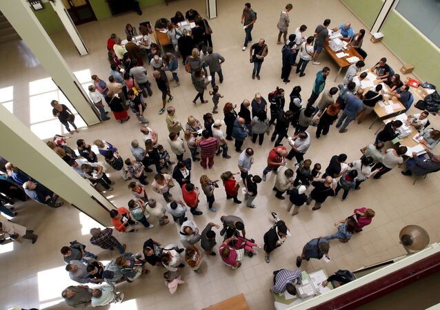 People line up to cast their ballots at a polling station during a regional parliamentary election in Barcelona, Spain, September 27, 2015