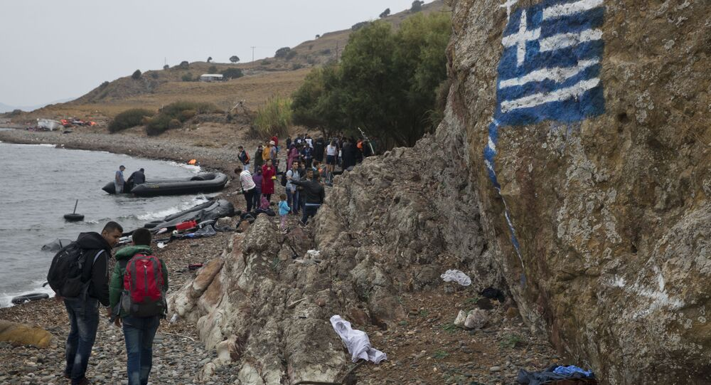 Greek flag is painted on a rock, as migrants arrive on the shores of the Greek island of Lesbos after crossing the Aegean Sea from Turkey on a inflatable dinghy , clamber over rocks on Tuesday, Sept. 22, 2015