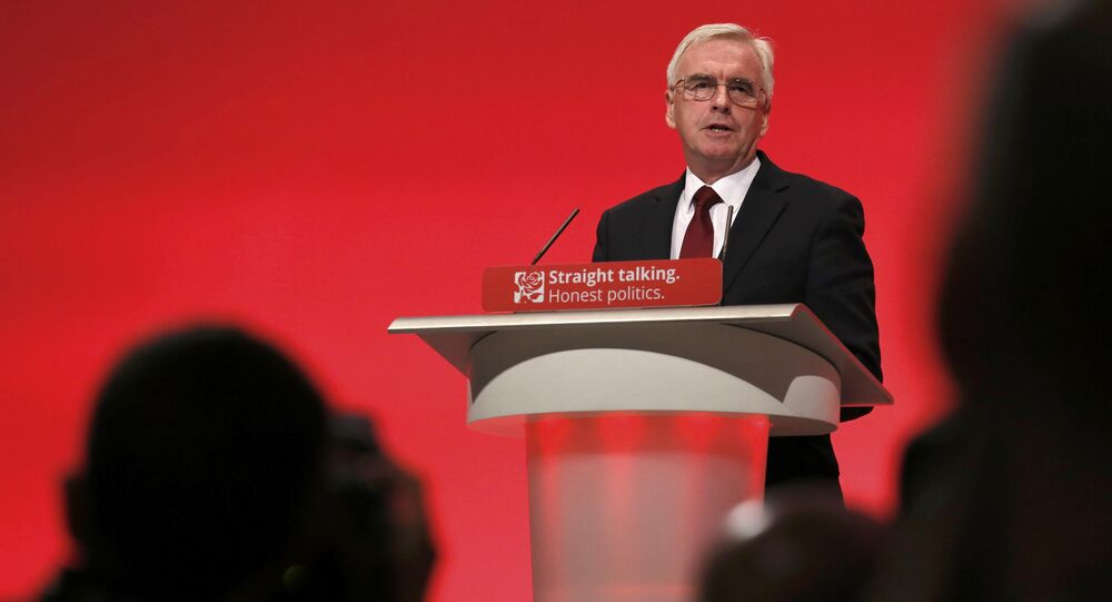 Members of the media photograph Britain's shadow Chancellor of the exchequer John McDonnell as he speaks at the annual Labour Party Conference in Brighton, southern Britain 28 September, 2015