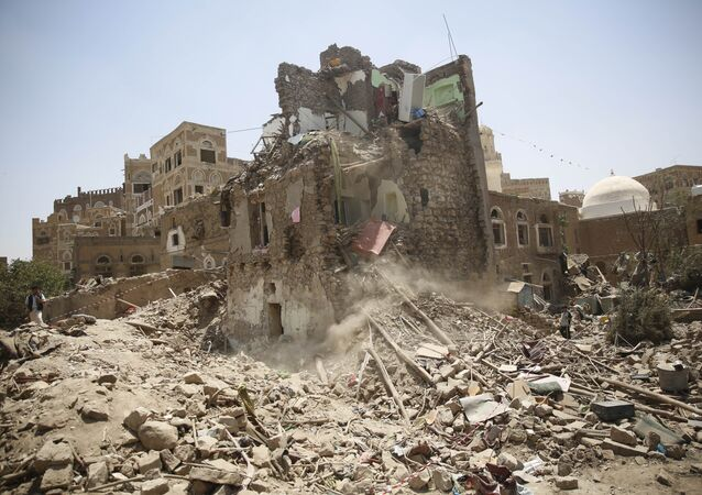 A man, left, stands guard amid the rubble of a house damaged in a Saudi-led airstrike in Sanaa, Yemen, Saturday, Sept. 19, 2015.