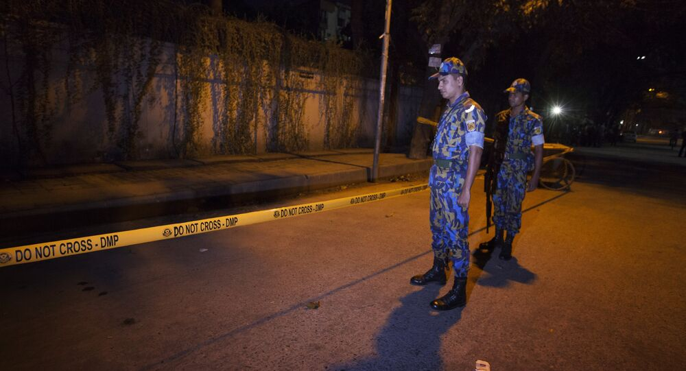 Bangladeshi police officers stand guard on September 28, 2015 at the site where an Italian charity worker has died after being shot by attackers in Dhaka