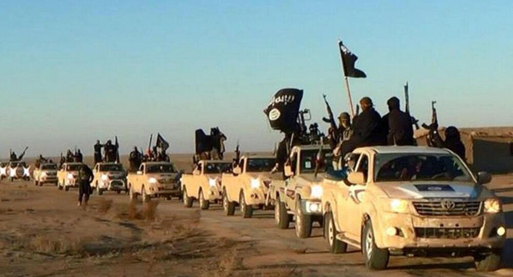 In this undated file photo released by a militant website, which has been verified and is consistent with other AP reporting, militants of the Islamic State group hold up their weapons and wave its flags on their vehicles in a convoy on a road leading to Iraq.