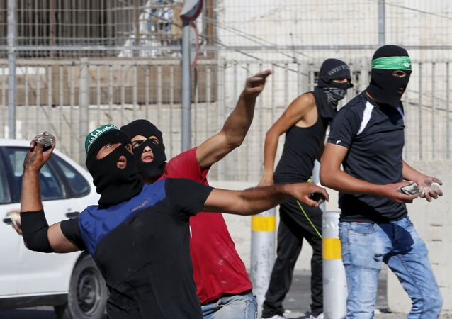 Palestinians hurl stones towards Israeli border police during clashes at a checkpoint between Shuafat refugee camp and Jerusalem September 18, 2015