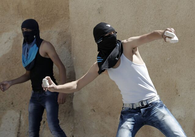 A masked Palestinian youth throws stones towards Israeli security forces during clashes