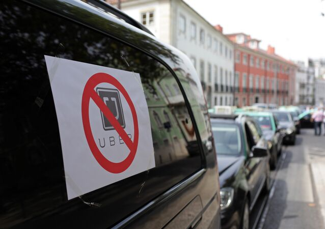Taxis with signs against the Uber ride-hailing service clog a street in Lisbon while moving at a slow pace in protest, Tuesday, Sept. 8 2015