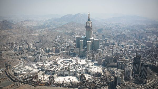 In this aerial photo made from a helicopter, the Abraj Al-Bait Towers with the four-faced clocks stands over the holy Kaaba, as Muslims encircle it inside the Grand Mosque, during the annual pilgrimage known as the hajj, in the Muslim holy city of Mecca, Saudi Arabia, Friday, Sept. 25, 2015. - Sputnik International