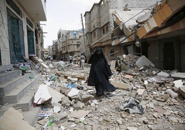 A woman walks amid the rubble of houses destroyed by a Saudi-led airstrike in Sanaa, Yemen, Monday, Sept. 21, 2015