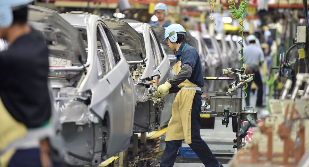 People work on the production line of the Toyota Motor Prius at the company's Tsutsumi plant in Toyota, Aichi prefecture on December 4, 2014