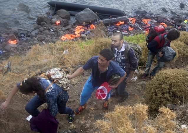 Syrian refugees climb a slope after arriving on an overcrowded dinghy under heavy rainfall on the Greek island of Lesbos after crossing a part of the Aegean Sea from the Turkish coast, September 28, 2015