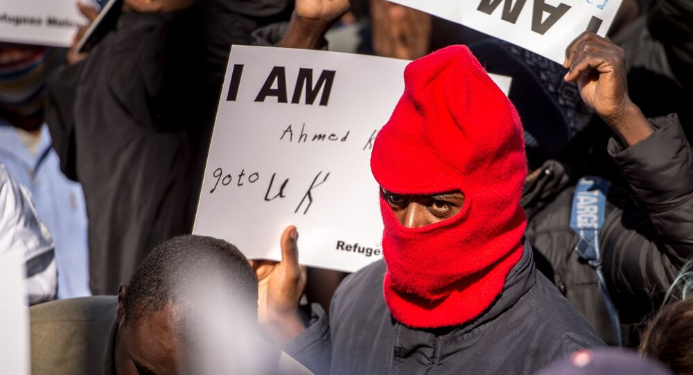 A migrant holds a placard reading 'I am Ahmed. Go to UK' as part of a rally of around 3000 migrants and members of associations aiding migrants including British associations, in the northern French port city of Calais (File)