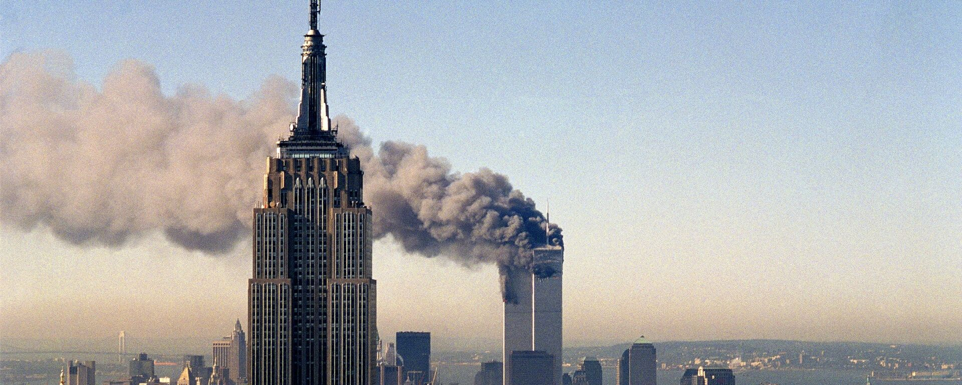 In this Sept. 11, 2001, file photo, the twin towers of the World Trade Center burn behind the Empire State Building in New York. - Sputnik International, 1920, 10.09.2021