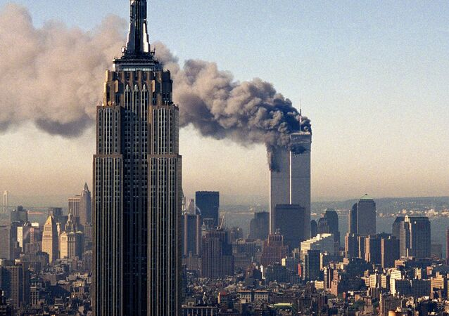 In this Sept. 11, 2001, file photo, the twin towers of the World Trade Center burn behind the Empire State Building in New York.