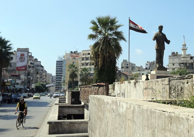 A man rides his bike past a statue of late Syrian president Hafez al-Assad, father of current President Bashar al-Assad, in the Syrian coastal city of Latakia on September 24, 2015