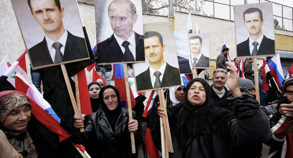Syrians hold photos of Syrian President Bashar Assad and Russian Prime Minister Vladimir Putin in Damascus, March 4, 2012.