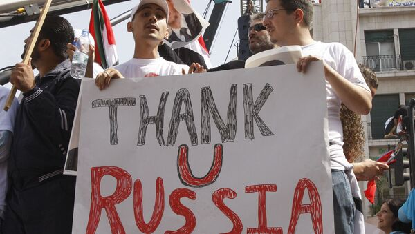 In this Oct. 12, 2011 file photo, supporters of the Syrian government hold a pro-Russian banner to show their support for President Bashar Assad and to thank Russia and China for blocking a U.N. Security Council resolution condemning Syria for its brutal crackdown, during a demonstration in Damascus, Syria. - Sputnik International