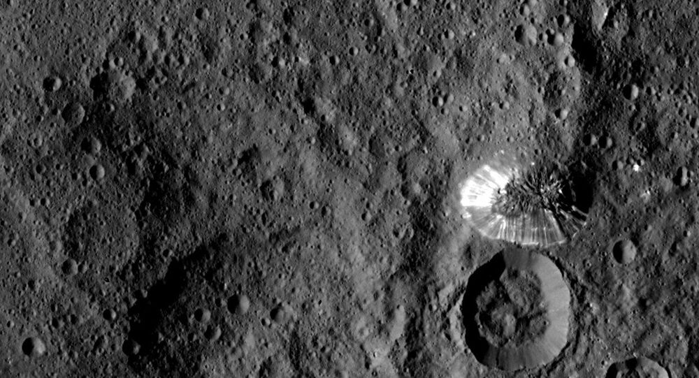 Ceres' four-mile tall mountain, photographed by Nasa's Dawn spacecraft from a distance of 915 miles (1,473 km), has a defined perimeter and shiny, streaked slopes.