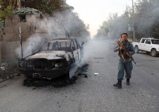 An Afghan policeman patrols next to a burning vehicle in the city of Kunduz, Afghanistan October 1, 2015