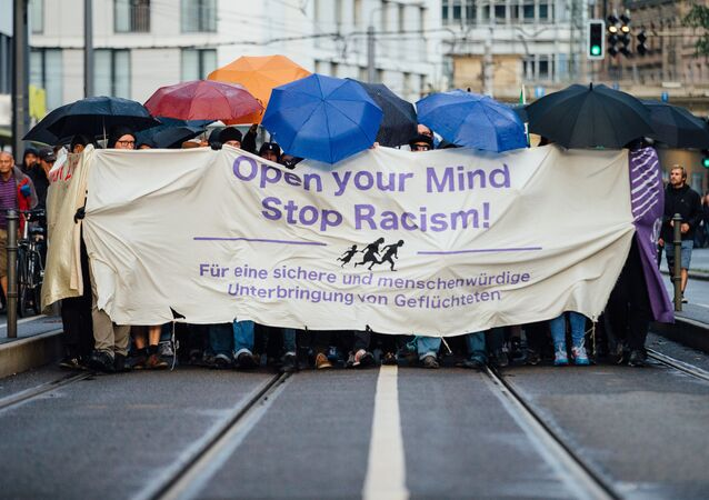 In this Monday July 27, 2015 picture demonstrators march through the city of Dresden, eastern Germany. They carried a banner reading: Open Your Mind - Stop Racism.