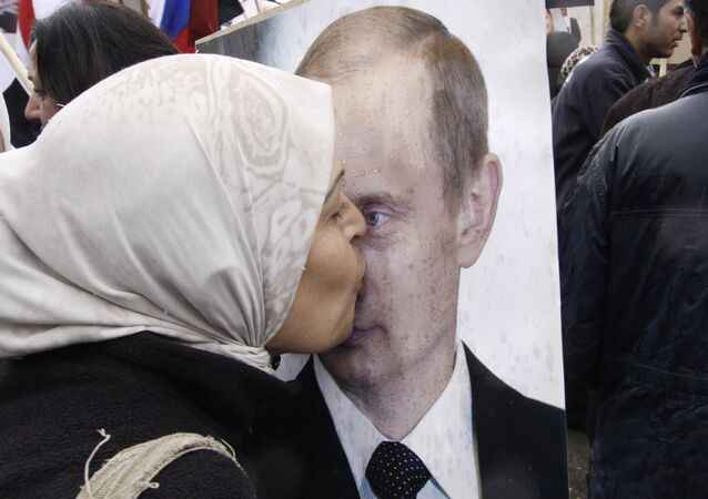 Syrian woman kisses a poster of Russian President Vladimir Putin during a pro-Syrian government protest in front of the Russian Embassy in Damascus, Syria