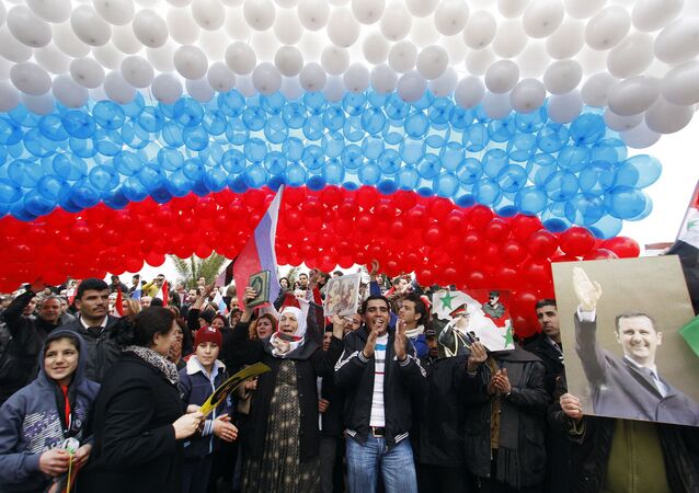 Pro-Syrian government protesters gather under a large Russian flag made with balloons in Damascus, Syria