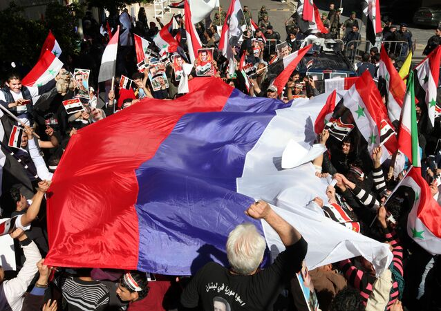 Syrian protesters wave a large Russian flag during a demonstration