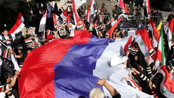 Pro-Syrian regime protesters wave a large Russian flag during a demonstration - Sputnik International