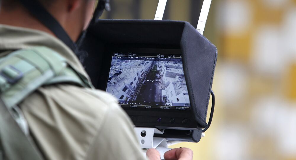 An Israeli soldier uses an unmanned surveillance drone to monitor Palestinian stone throwers.