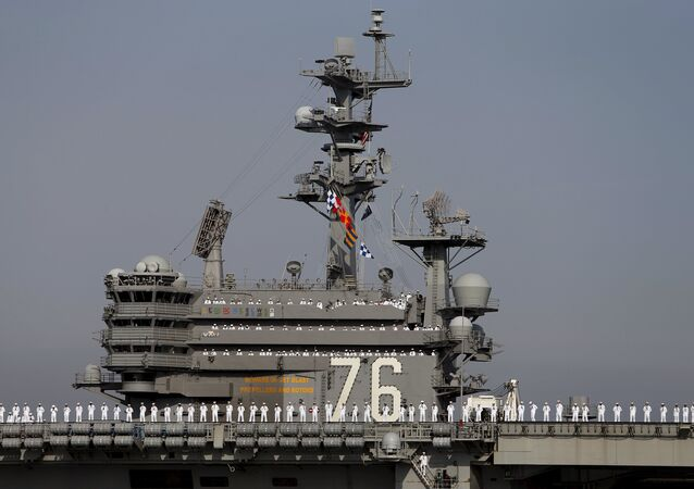 The crew members of the USS Ronald Reagan, a Nimitz-class nuclear-powered super carrier, stand at attention as it arrives at the U.S. naval base in Yokosuka, south of Tokyo, Japan