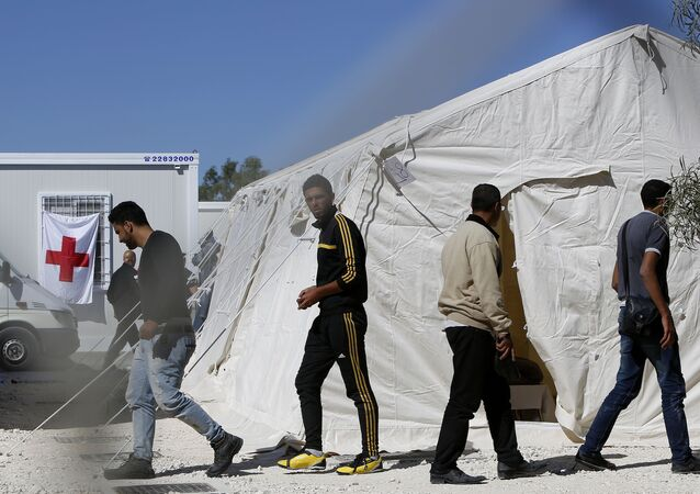 Migrants walk by the tents at a reception camp at Kokkinotrimithia village outside Cyprus' capital Nicosia