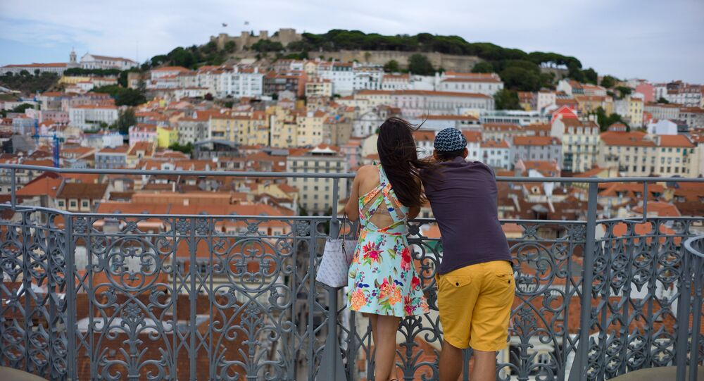 A young couple enjoys the view from the top of Lisbon's 1902 Santa Justa lift Friday.