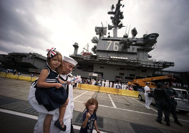 A crew member of the US navy aircraft carrier USS Ronald Reagan stands with his family at the US naval base in Yokosuka, Japan.