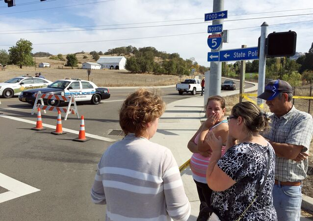 People gather at a road block near the entrance to Umpqua Community College, in Roseburg, Ore., Thursday, Oct. 1, 2015, following a deadly shooting at the campus.