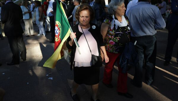 A supporter of the Portuguese Socialist Party carries a Portuguese flag while waiting for the arrival of the party leader Antonio Costa during a campaign action in Lisbon Tuesday, Sept. 29 2015. - Sputnik International