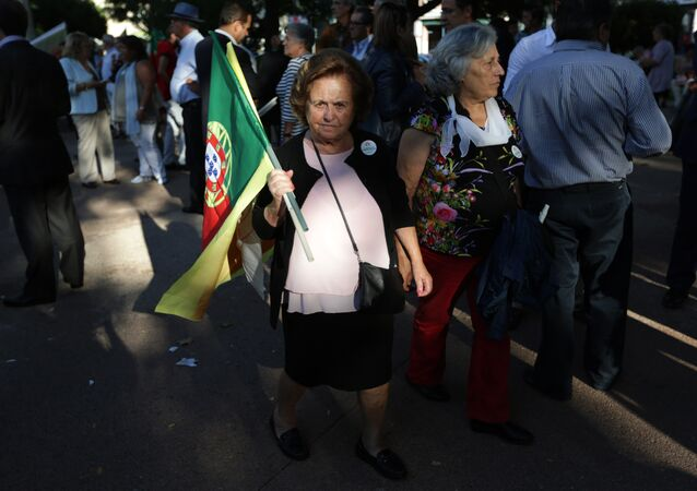 A supporter of the Portuguese Socialist Party carries a Portuguese flag while waiting for the arrival of the party leader Antonio Costa during a campaign action in Lisbon Tuesday, Sept. 29 2015.