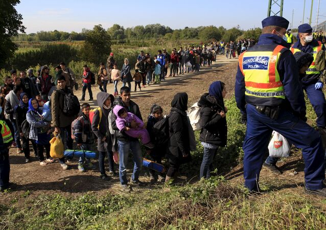 Migrants queue to board a train at the railway station in Zakany, Hungary October 1, 2015.