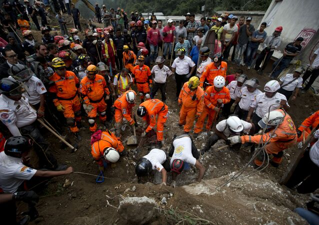 Rescue workers and firemen search for survivors at the the site of a landslide in Cambray, a neighborhood in the suburb of Santa Catarina Pinula, about 10 miles east of Guatemala City, Friday, Oct. 2, 2015.