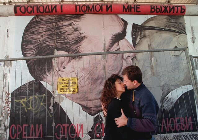 Two unidentified tourists kiss in front of a painting on one of the rare remaing parts of the Wall in Berlin, in October 1995