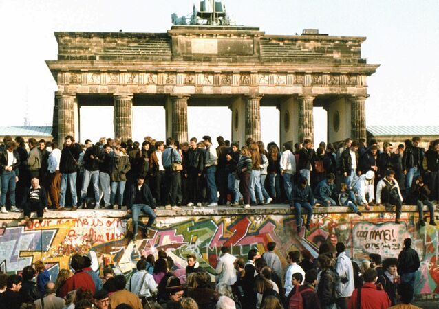 People walking on the Berlin wall in front of the Brandenburg gate after opening one day before, Nov. 10, 1989