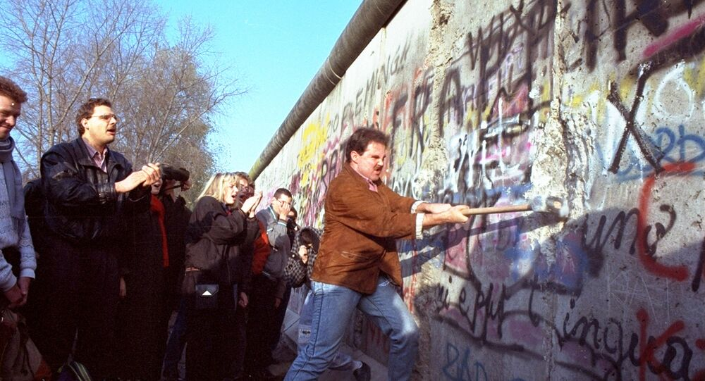 An unidentified West Berliner swings a sledgehammer, trying to destroy the Berlin Wall near Potsdamer Platz, on 12 November 1989, where a new passage was opened nearby