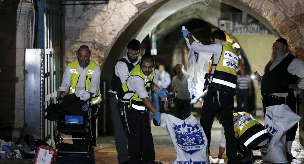 Members of the Zaka Rescue and Recovery team clean the scene where a Palestinian was shot dead after he stabbed and killed two people in Jerusalem's Old City October 3, 2015
